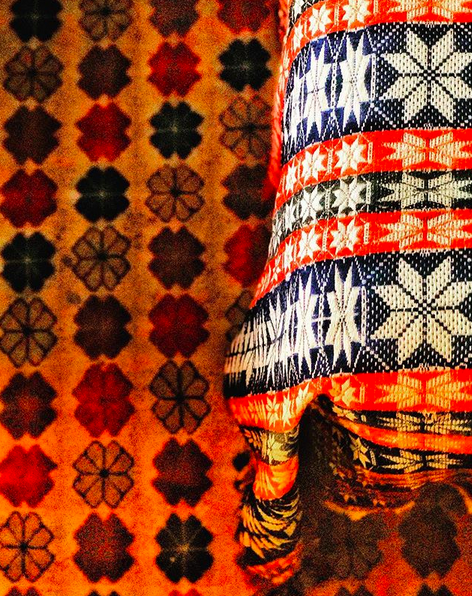 A close up photo of the corner of a bed with a scandinavian inspired design of white flowers or stars agains orange and navy stripes, with an orange rug with geometric flowers on it.