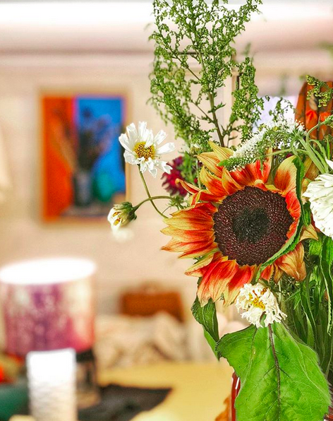 A photograph of a bedroom focused on a bouquet of flowers slightly past their best. The rest of the room is in soft focus, but you can make out a lamp on a dresser, and a painting of a vase of flowers on the wall.