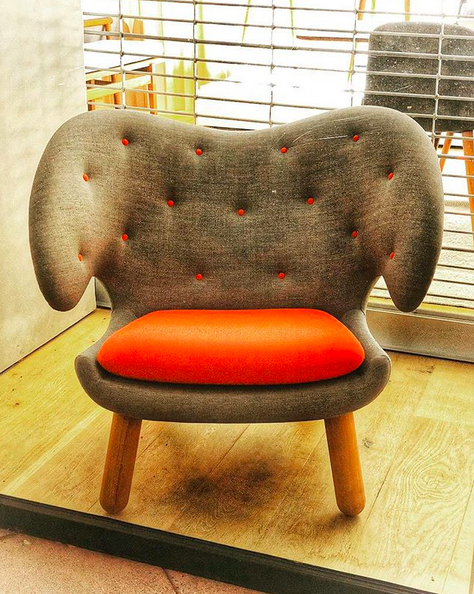 A photo of a modern arm chair in a shop window. The chair is fantastic, with a grey fabric covering, tufted using bright orange buttons that match the bright orange seat cushion.