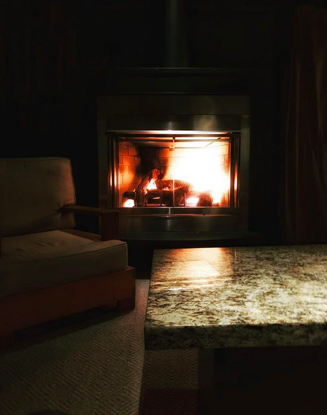 A night photo of a dark living room with a roaring fire in the fireplace.