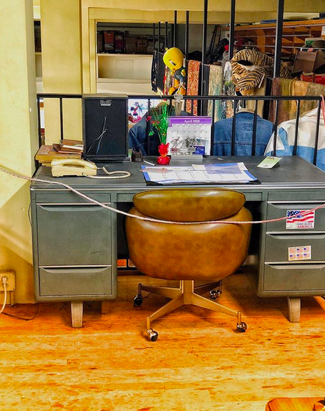 A metal midcentury desk with a leather rolling chair in an upper balcony of a building, with a wide assortment of nonsensical items strewn about.