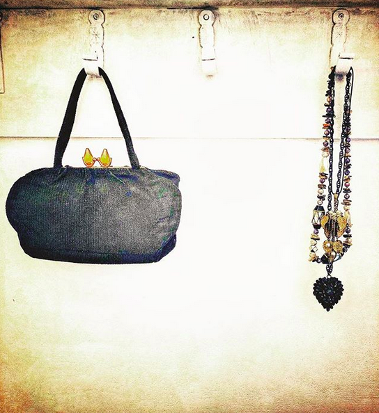 A black purse and black beaded necklace hanging on off-white metal hooks against an off-white wall.