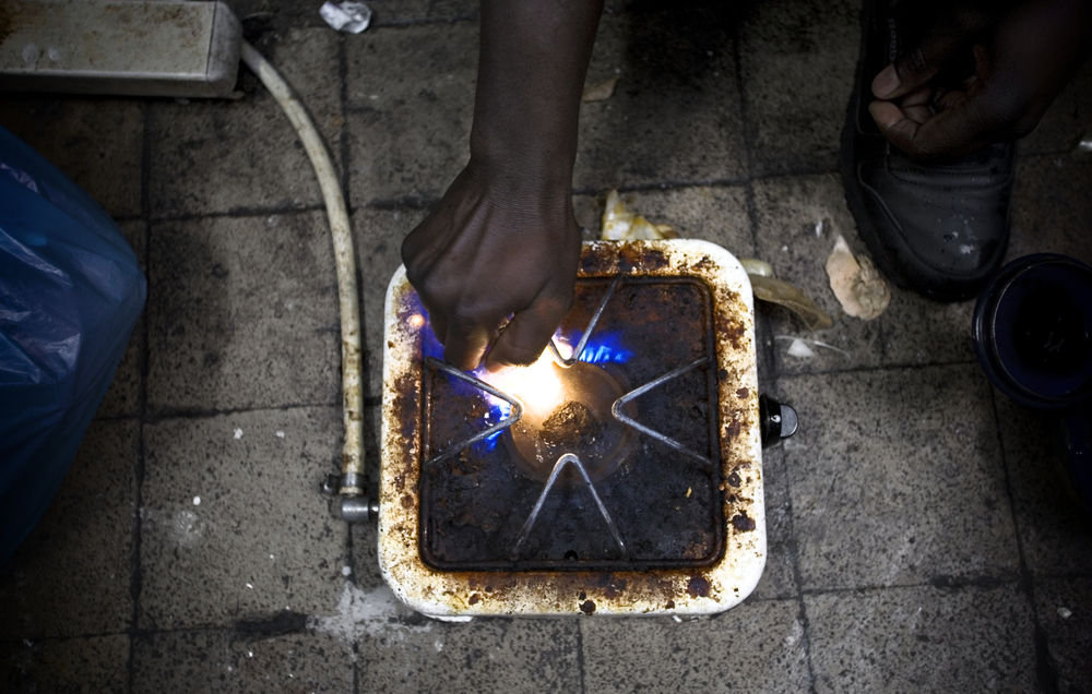 Diombana Bndjougou, a 25 year old man from Mali, lights a fire on a hot plate connected to a tank of petrol to begin cooking dinner.