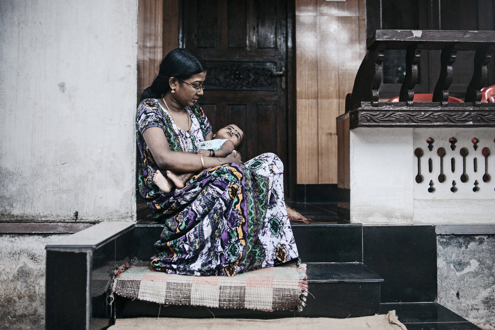 Diya holds her 1 yr old daughter. The father, a laborer in the U.A.E., has yet to meet his child. Kerala, India.