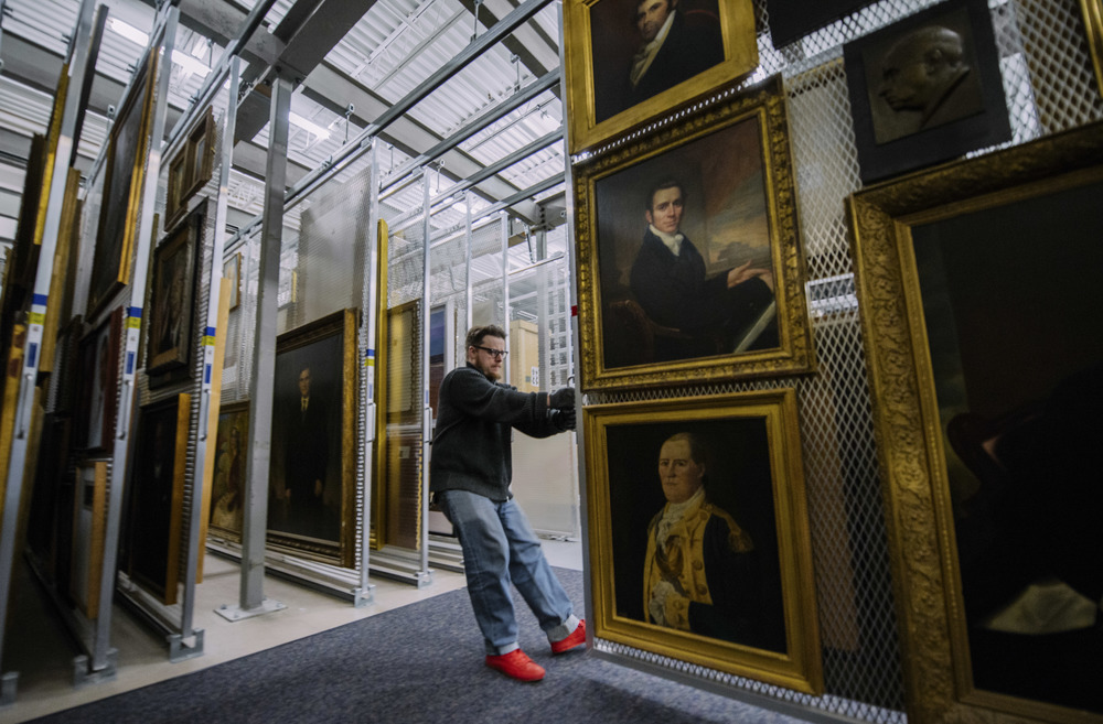 "Smithsonian National Portrait Gallery Museum Technician Todd Gardner moves paintings at NPG's warehouse ""Apollo"" in Largo, MD, Tuesday, Feb. 23, 2016. Artworks are stored in the facility when they are not in display."