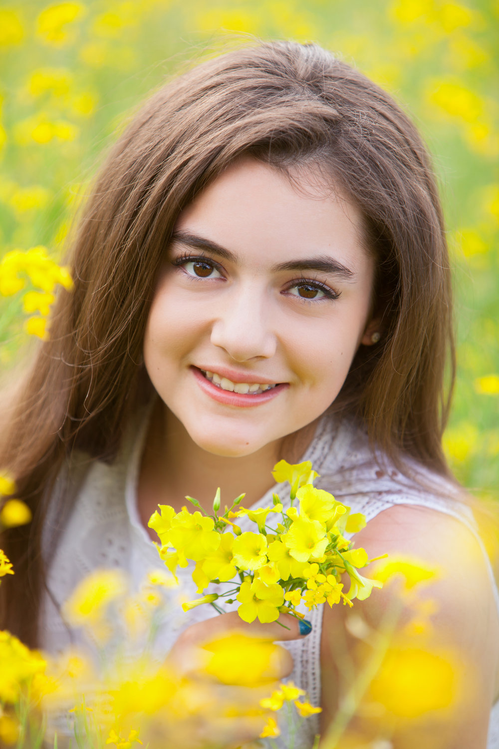 Pretty girl with long brown hair in the flowers