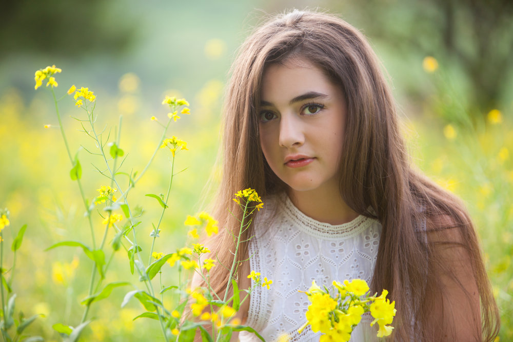 Pretty girl with long brown hair outdoors in the flowers