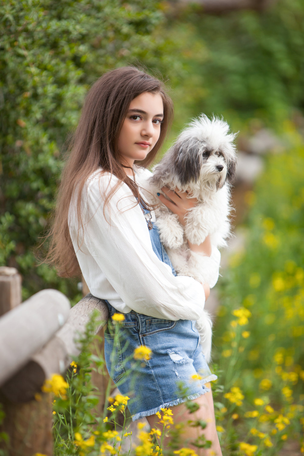 Prettyirl with long brown hair in the flowers with her dog