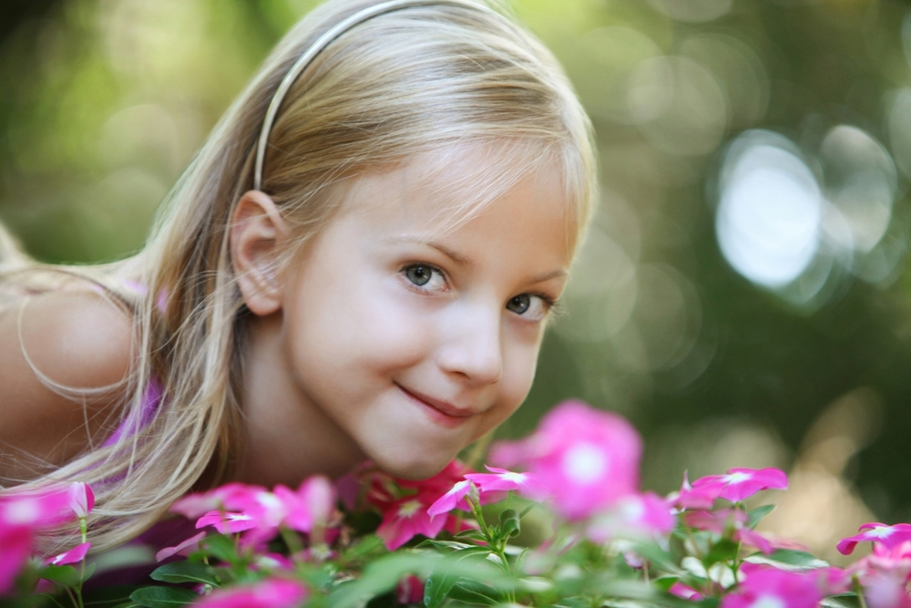 Pretty young girl outdoors in the flowers
