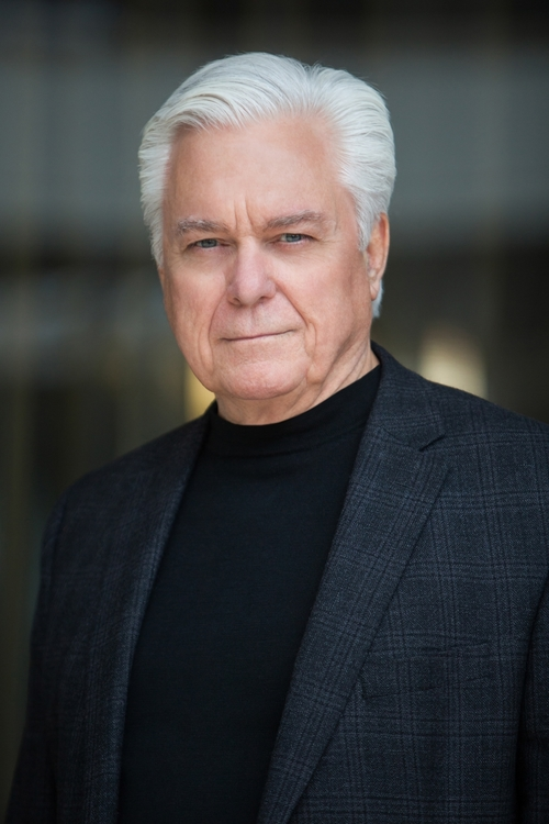 corporate headshot of man with gray hair