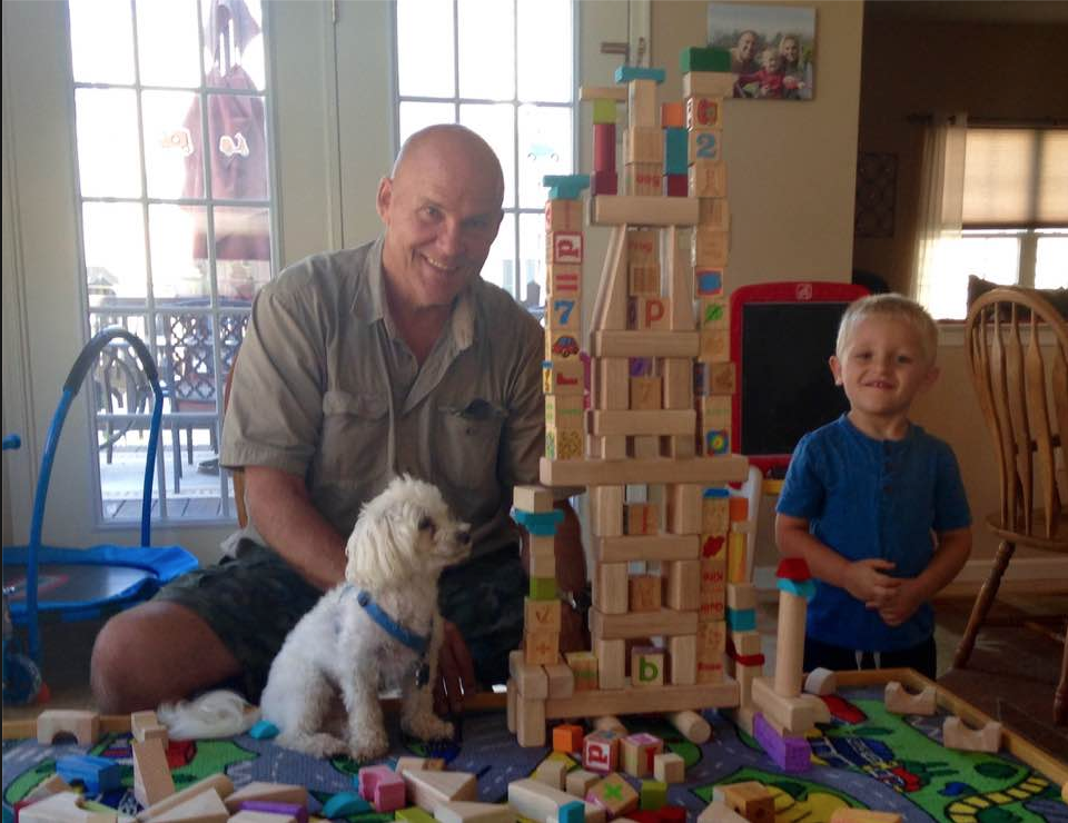 Farmer Fred, Bailey, and his grandson building a block tower