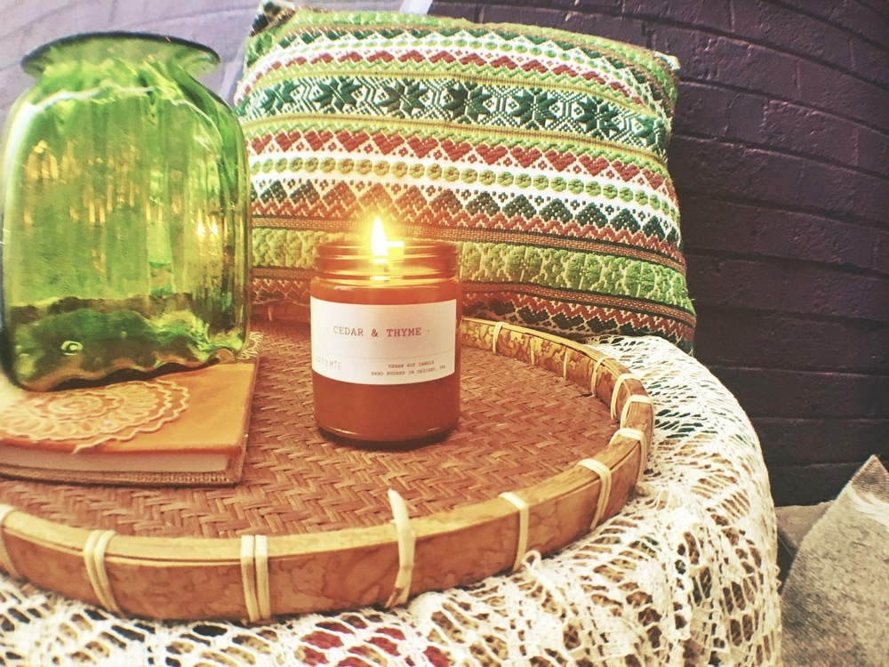 Artume cedar & thyme candle; 9oz $22 12oz $28 small green embellished throw pillow; $26