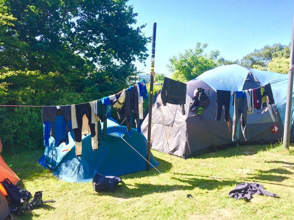 We had to think outside of the box for some things whilst camping. Here we set up a washing line to dry our sailing kit using an old mast and a mainsheet strung between a lamp post and car trailer. It worked surprisingly well!