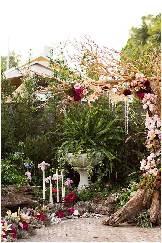 grace and serendipity, ashley victoria photograpy, fiore - the lacy oyster - one sided arch with crepe myrtle, reds, pinks, pearls and flowers - ceremony area with one sided arch, tapered candles, intimate and romantic setting