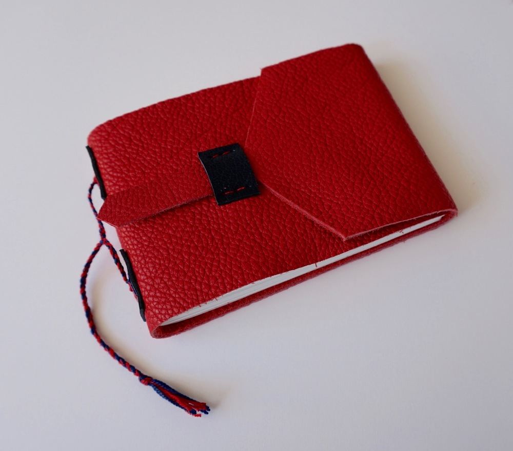 Here is a red leather pocket book, sewn in a similar manner to the cloth book.