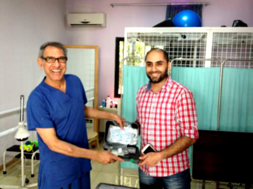 Dr Francis delivers a portable neuro-muscular electrical stimulator to the Medical Centre in Tripoli.