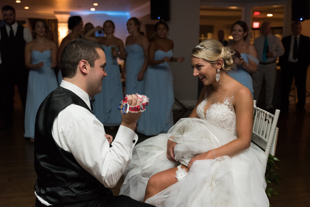 GARTER TOSS - There's usually a lot of laughter while the groom is looking for the garter under the bride's dress.