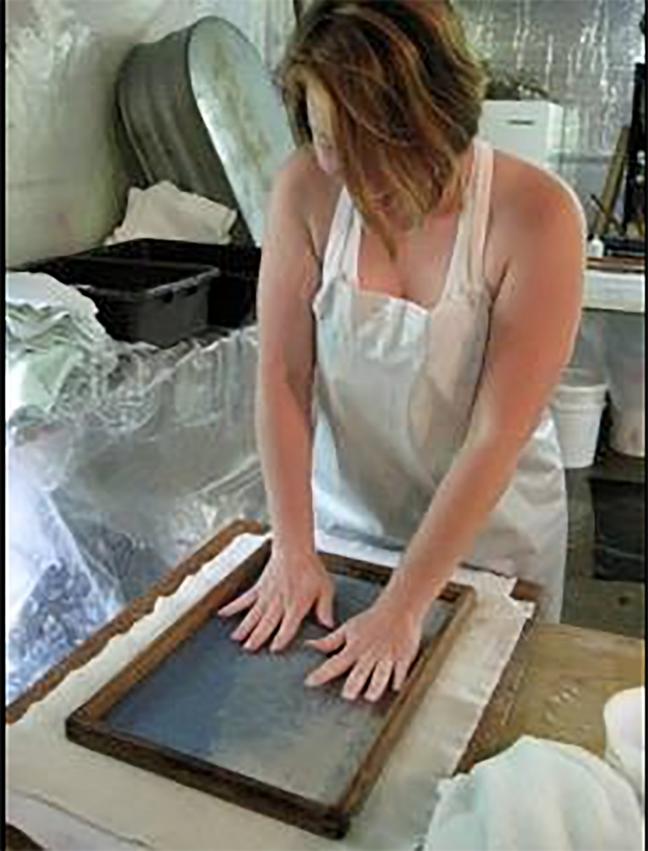 Carmela is couching a sheet of handmade paper onto wet felts in the introduction to papermaking workshop. This paper is made with blue jean pulp, abaca and other plant fibers.