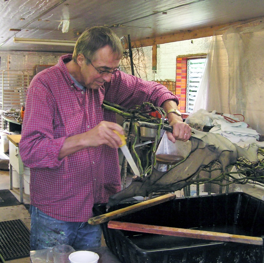Henry at work applying pulp to smaller areas of his sculpture with a turkey baster.