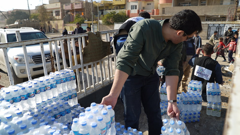 Iraq Country Director for HERA, Ammar, distributing water