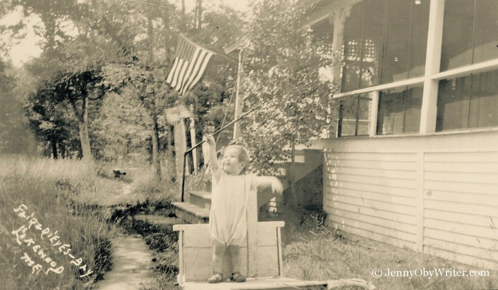 """A child waves the American flag outside one of the small cottages that were part of the """"resort"""" at Fairgrieve's Bay on Lake Wesserunsett."""