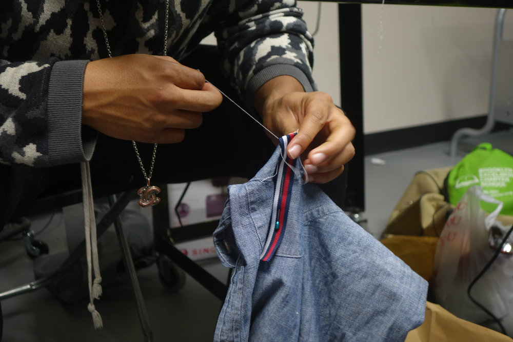 Rob hand sewing fabric onto a J. Crew button-up shirt.