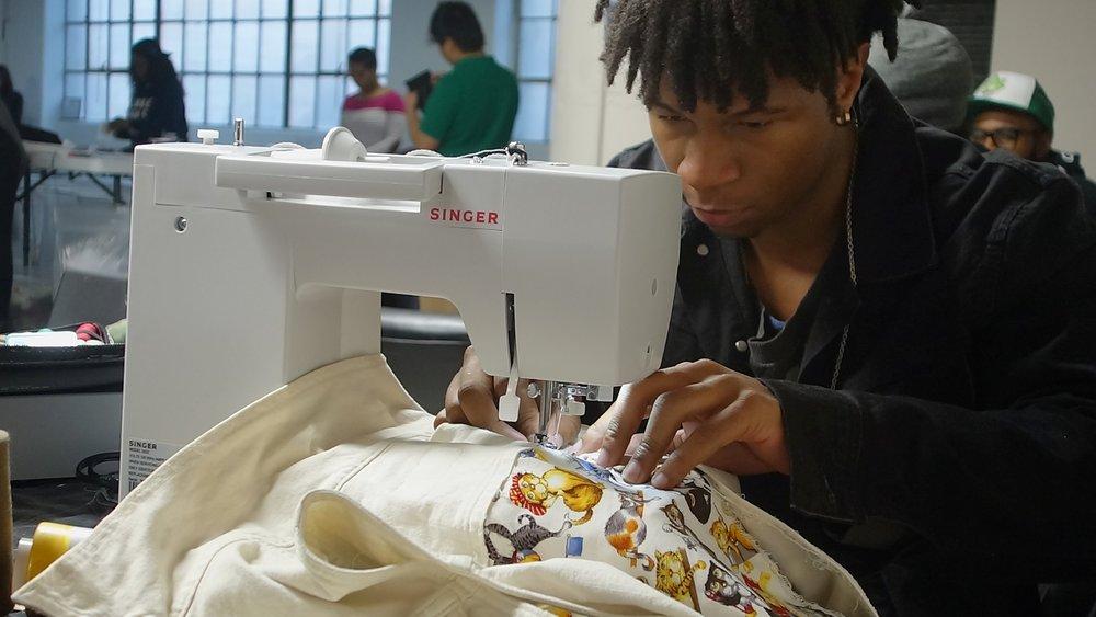 Rob machine sewing cat fabric onto a denim jacket.