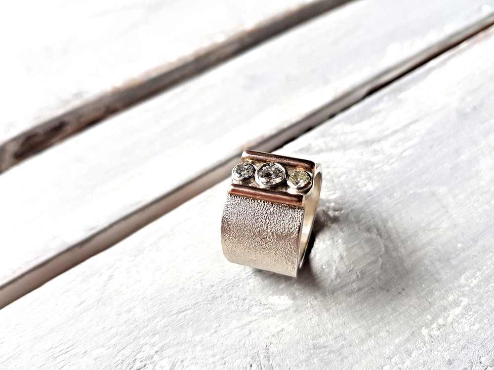 Carly's Ring  Three stunning diamonds, one from her Grandmother's ring and two from her Mum's earrings. They were reset nestled in-between 9ct Rose gold on the Rippled textured sterling silver band.