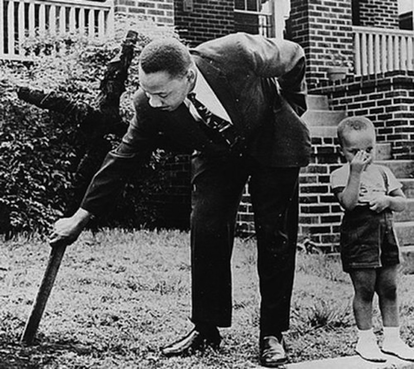 April 1960: King pulling a burned cross from his yard. This picture also appears in the book.