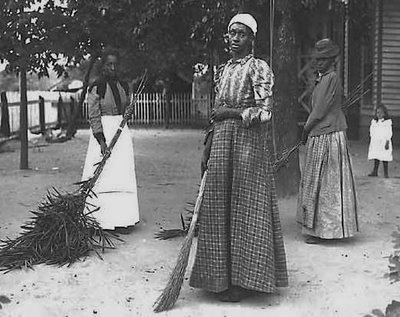 African-American women sweeping a yard in Belton, North Carolina, 19th century American South. Description: Three women hold brooms, sweeping a bare-surfaced yard. A child stands in the background in front of a house. Source:  U.S. History in Context