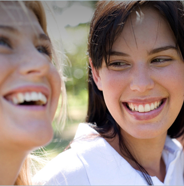 two adult female friends laughing after recovering from ptsd and trauma-related issues