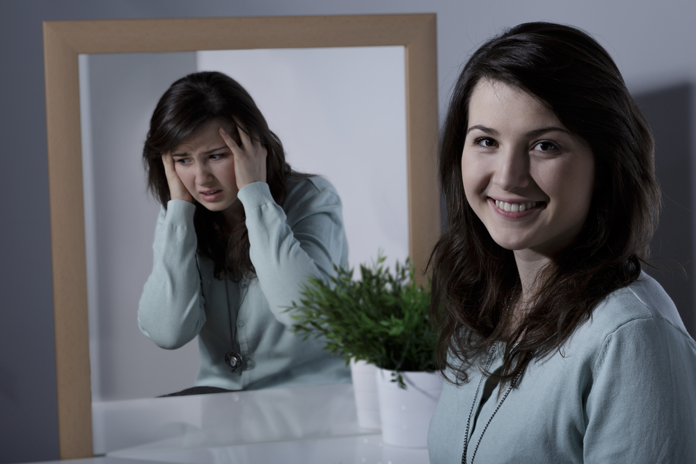 young female adult with bipolar disorder looking in the mirror