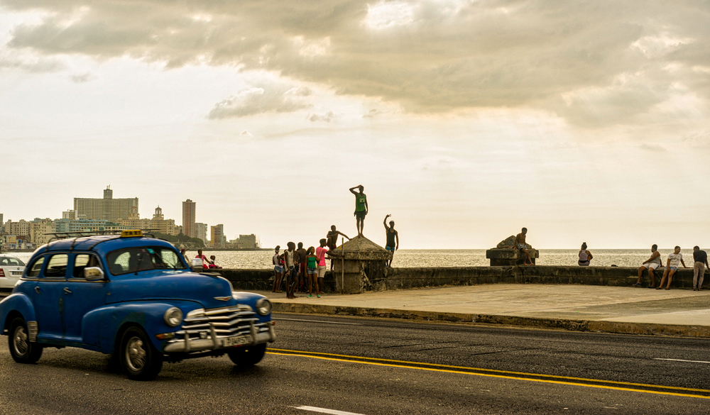 An old car drive along the Malecon in Havana, Cuba.