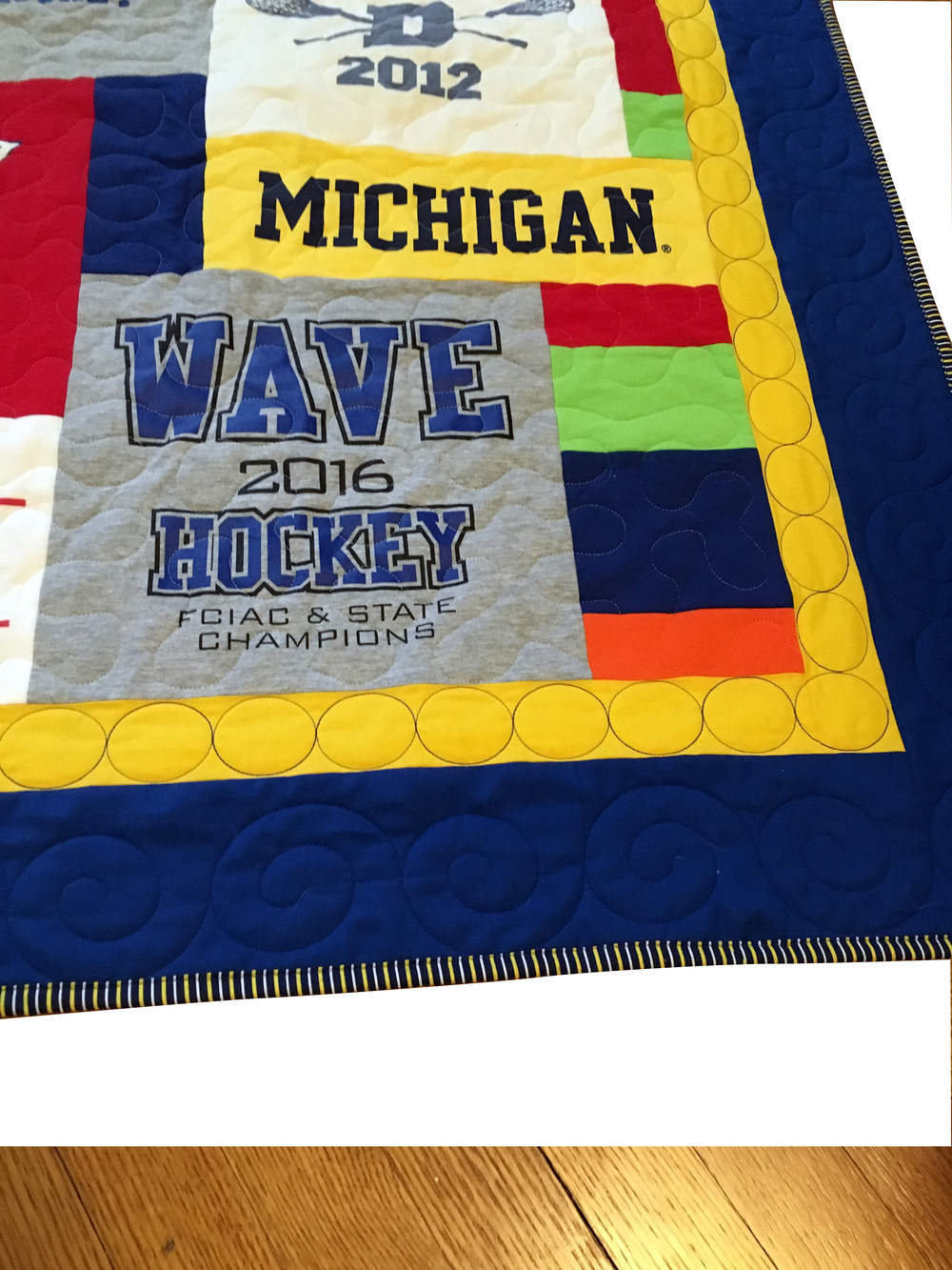 Double blue and yellow border with custom quilting and a state title