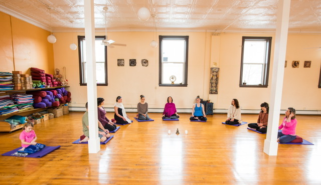 Michelle Miller (middle, in magenta wrap) leads a meditation at the Yoga Center in Amherst. (Photo credit: Amherst Mindfulness)