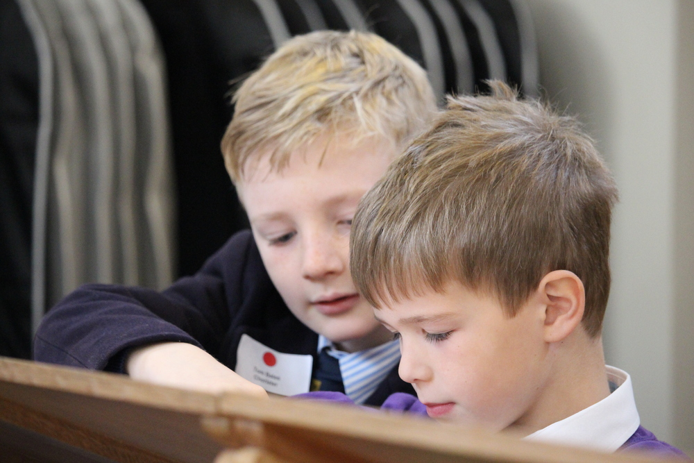 A current junior chorister guides a young prospective chorister during 'Be a Chorister for a Day'