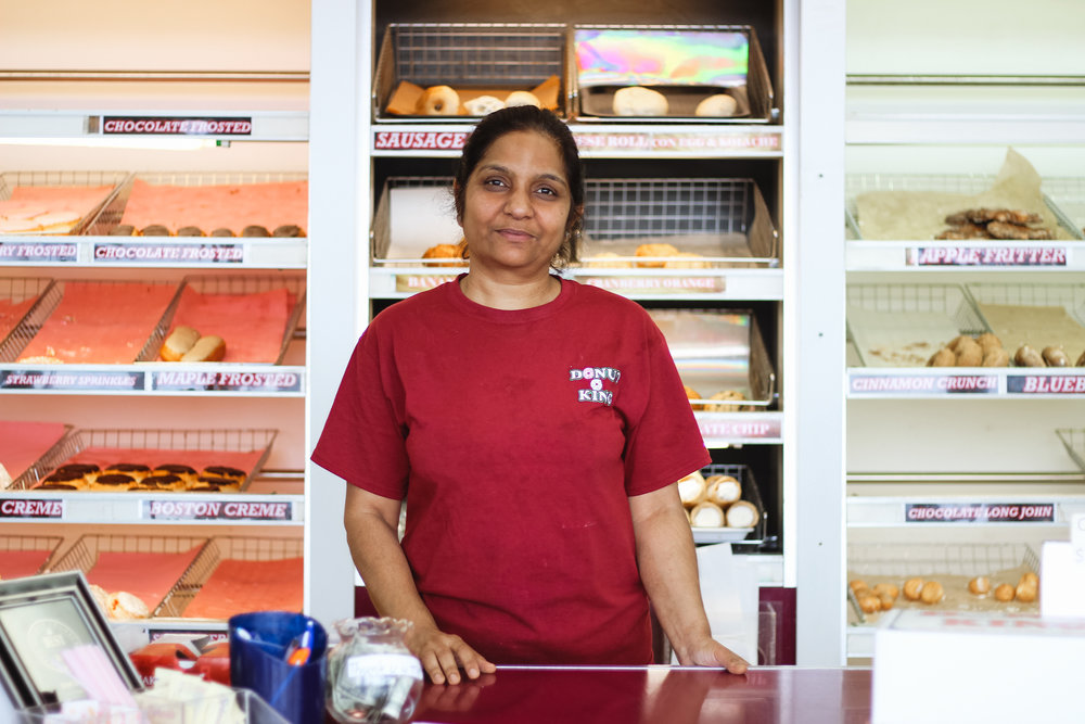 Dipti Patel stands behind the counter of the Donut King shop on Lindsey Street after the morning rush. She and her husband, Sanjay Patel, bought the shop in 1994, when it was a Dunkin' Donuts franchise.