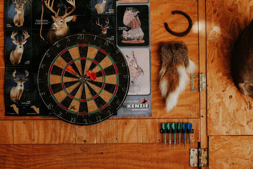 A dart board hangs on a wall in Sherman's shop.