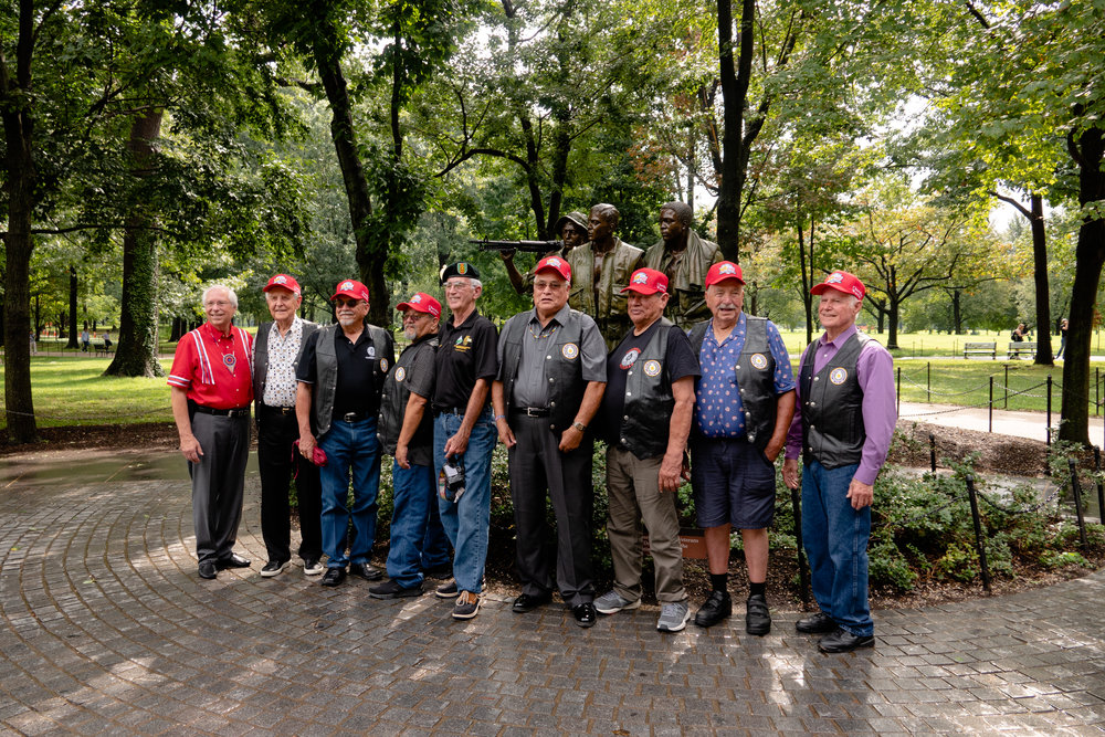 The group of veterans on the 2018 Warrior Flight stop to take a group photo in front of The Three Servicemen statue at the Vietnam Veterans Memorial.
