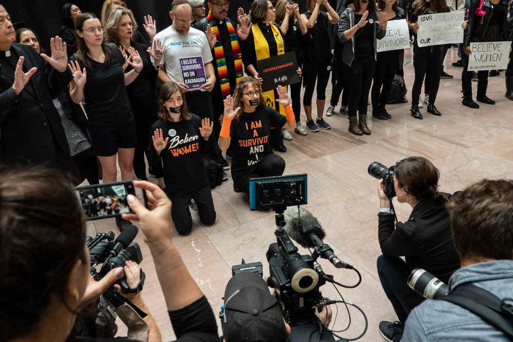 Journalists photograph protesters in the Hart Senate Office Building.