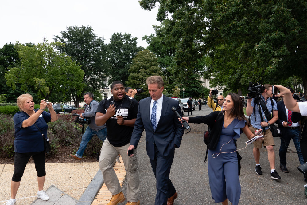 Senator Jeff Flake of Arizona, a member of the Senate Judiciary Committee, remains silent as protesters and members of the press ask him about the committee's hearing.