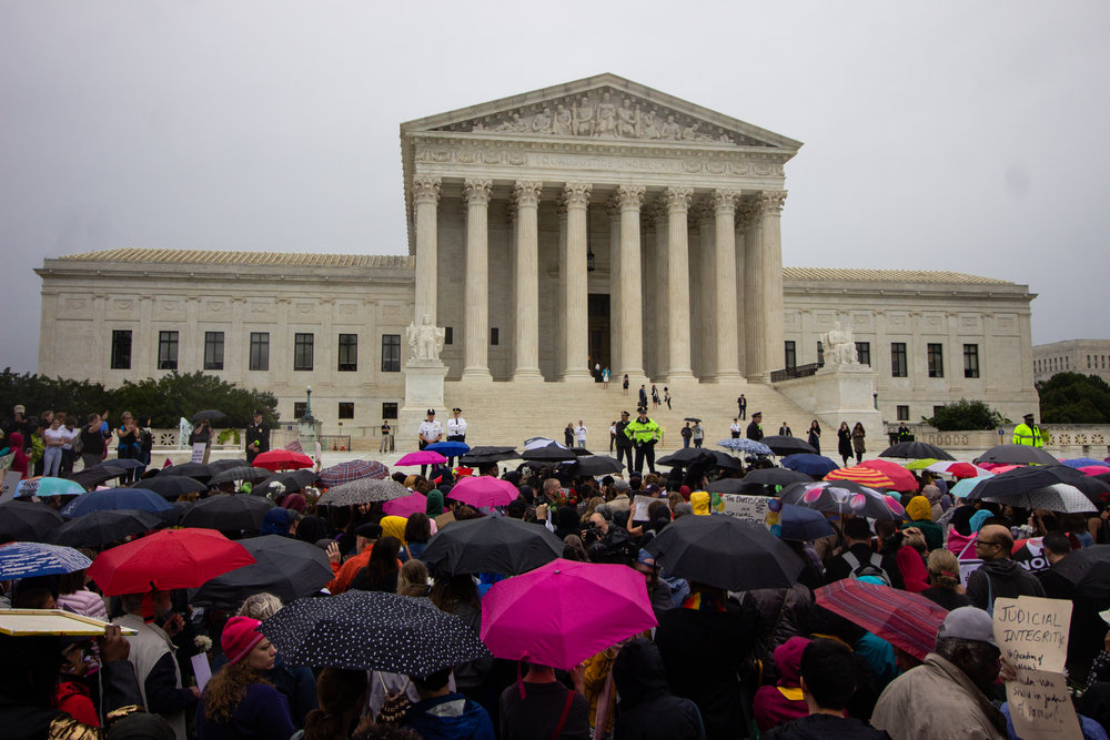 Lifting umbrellas against the rain, protesters gathered in front of the Supreme Court building to demonstrate support for Christine Blasey Ford while she testified before the Senate Judiciary Committee.