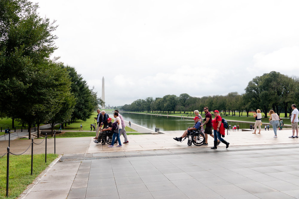 A pair of veterans are pushed in wheelchairs past the Reflecting Pool at the Lincoln Memorial.
