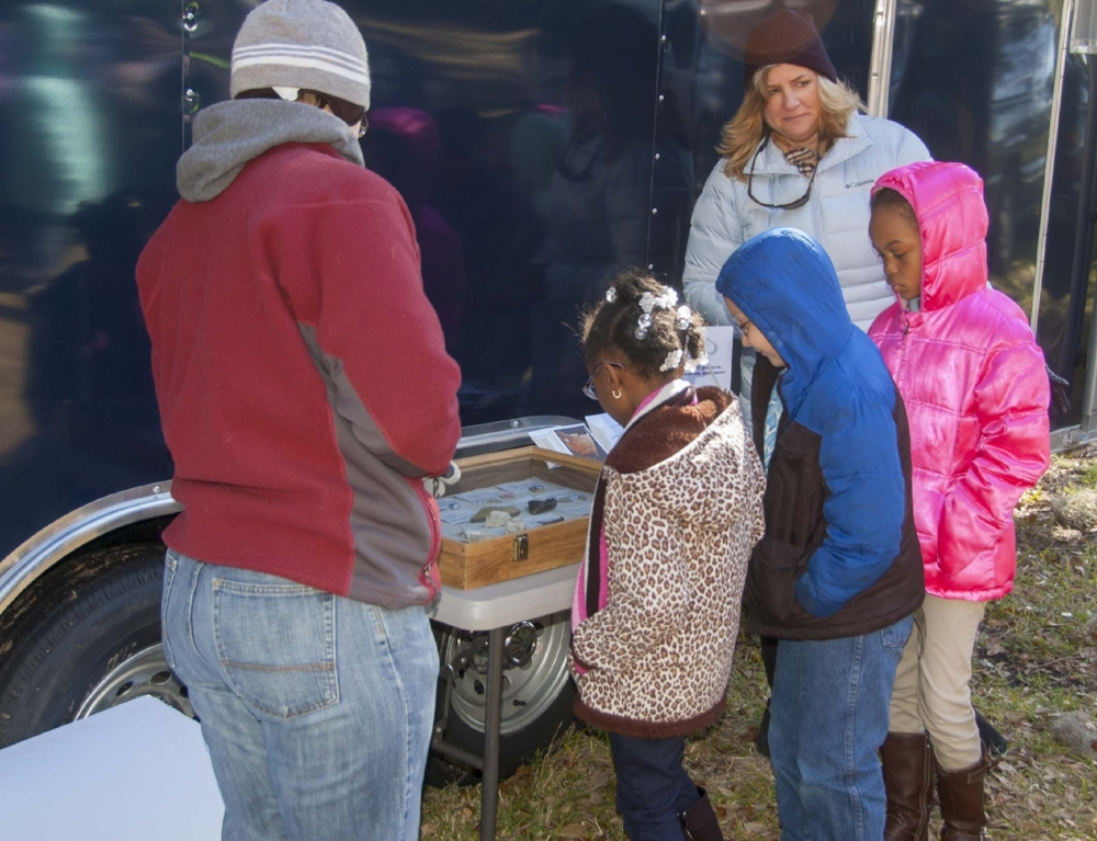 "A group of schoolchildren attending one of the ""public day"" events held during the excavation marvel at some of the artifacts discovered at Fort Frederick and the surrounding area, home to ""Smith's Plantation"" during the 1800s."
