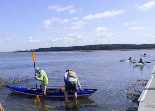 Club member Bill Dickinson demonsttrates the right way to enter and exit a kayak.  photo by Nancy Stills, Sun City Hilton Head Kayak Club