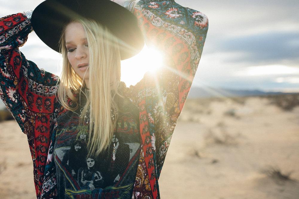 Boho styled senior photo in the desert with sun flare.