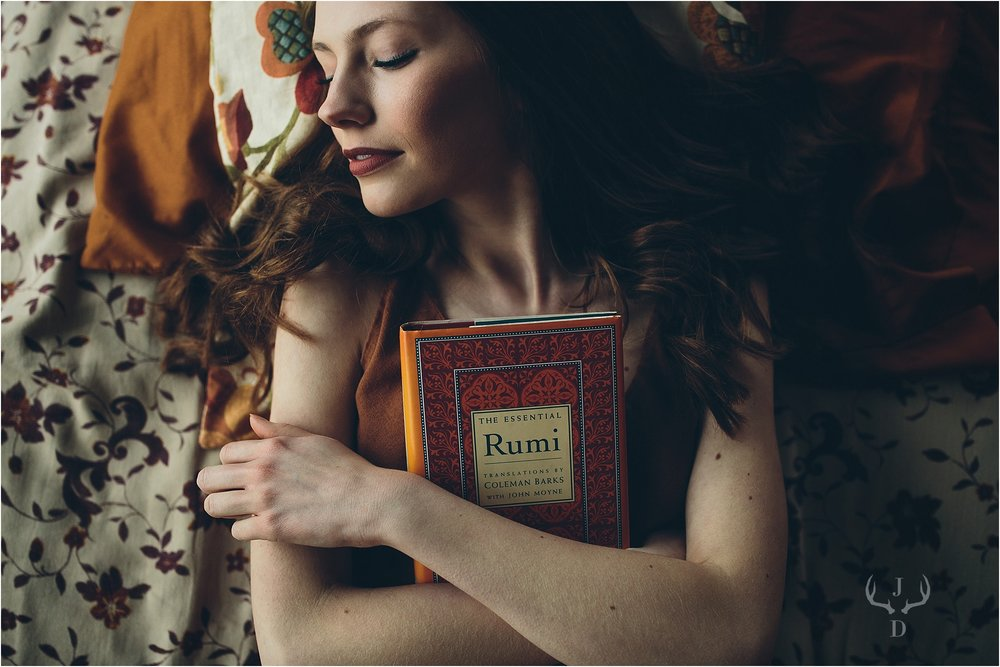 Senior picture lying down with Rumi book taken in Madison, WI.