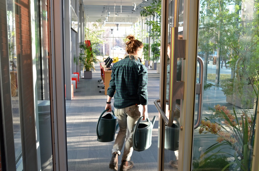 "Coburn carries two watering cans from the tap in the greenhouse to the plants in the lobby of the new wing. ""There's no hose out here,"" she tells me."