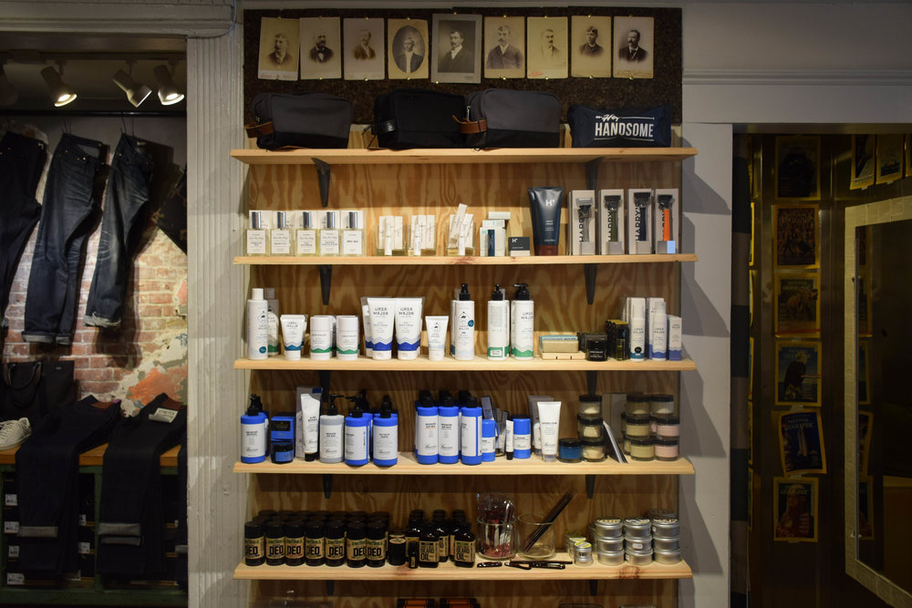 The apothecary shelves are lined with American made lotions, tonics, and waxes, from some of the country's premier grooming brands, like URSA Major, Harry's, and Baxter of California.