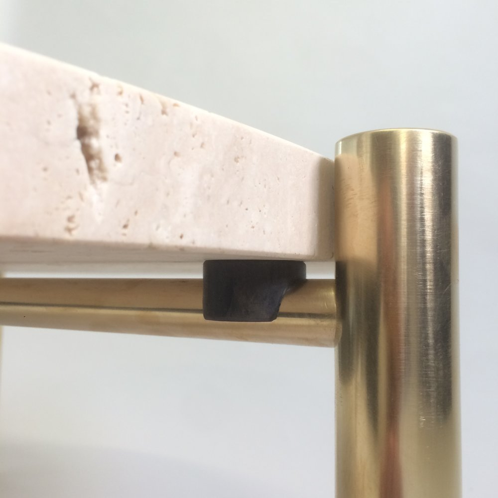 Marble coffee table detail: the client chose to use unfilled marble to give the table a raw finish. The marble slab sits on a rubber support atop the brass leg.
